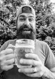 Mann, der Sommertag des Bieres genie?end hei?en sich entspannt Bier- und Alekonzept L?schen Sie Manngriff-Becherk?lte Durst Hippi stockfotografie