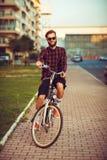 Mann in der Sonnenbrille, die ein Fahrrad auf Stadtstraße reitet Stockbilder