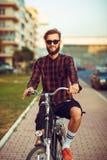 Mann in der Sonnenbrille, die ein Fahrrad auf Stadtstraße reitet Stockfotografie