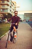 Mann in der Sonnenbrille, die ein Fahrrad auf Stadtstraße reitet Lizenzfreie Stockfotos