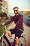 Mann in der Sonnenbrille, die ein Fahrrad auf Stadtstraße reitet Stockfoto