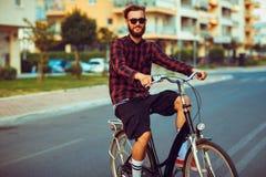 Mann in der Sonnenbrille, die ein Fahrrad auf Stadtstraße reitet Lizenzfreie Stockbilder