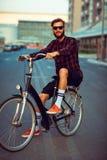 Mann in der Sonnenbrille, die ein Fahrrad auf Stadtstraße reitet Stockbild
