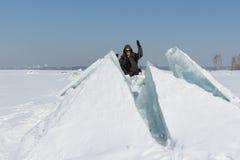 Mann in der Sonnenbrille, die ein gebrochenes Eis auf einem Fluss klettert Lizenzfreies Stockfoto