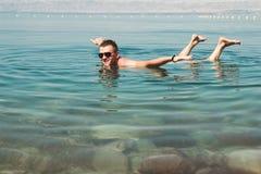 Mann in der Sonnenbrille wirft wie Flugzeug auf Oberflächentotem Meer auf Freizeit, Ferien, Wellnesstourismus, Erholungskonzept Stockbilder
