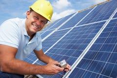 Mann, der Sonnenkollektoren installiert Lizenzfreies Stockbild