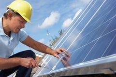 Mann, der Sonnenkollektoren installiert Stockfotos