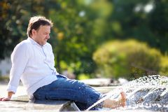Mann, der Spaß in einem Stadtbrunnen hat Lizenzfreies Stockbild