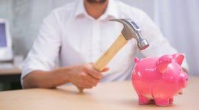 Mann, der Sparschwein mit Hammer bricht Lizenzfreie Stockfotos