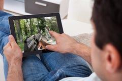 Mann, der Spiel auf Tabletten-PC spielt Stockbilder