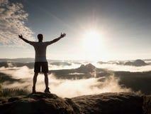 Mann an der Spitze eines Berges, der die nebelhafte Landschaft schaut Glauben Sie frei Stockbilder