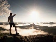 Mann an der Spitze eines Berges, der die nebelhafte Landschaft schaut Glauben Sie frei Lizenzfreie Stockbilder