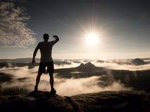 Mann an der Spitze eines Berges, der die nebelhafte Landschaft schaut Glauben Sie frei Stockfotos