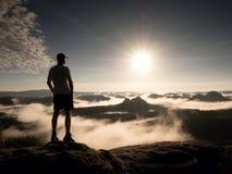 Mann an der Spitze eines Berges, der die nebelhafte Landschaft schaut Glauben Sie frei Stockfoto