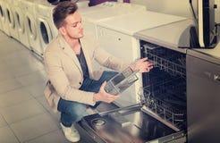 Mann, der Spülmaschine vorwählt Lizenzfreies Stockbild