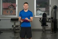 Mann in der Sport-Ausstattung nimmt Kenntnisse über Klemmbrett Stockbilder