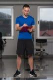 Mann in der Sport-Ausstattung nimmt Kenntnisse über Klemmbrett Stockfoto