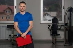 Mann in der Sport-Ausstattung nimmt Kenntnisse über Klemmbrett Lizenzfreie Stockbilder