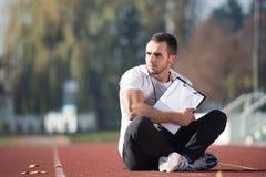 Mann in der Sport-Ausstattung nimmt Kenntnisse über Klemmbrett Lizenzfreie Stockfotografie