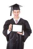 Mann in der Staffelungsrobe, die Tabletten-PC zeigt Lizenzfreies Stockfoto