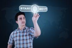 Mann, der Startknopf mit 2017 bedrängt stockbild