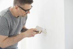 Mann, der an Steckdose arbeitet Lizenzfreie Stockfotografie
