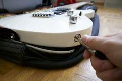 Mann, der Steckfassung in weiße E-Gitarre einfügt Lizenzfreie Stockbilder