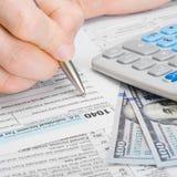 Mann, der Steuerformular 1040 Vereinigter Staaten von Amerika - 1 bis 1 Verhältnis ergänzt Lizenzfreies Stockfoto