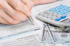 Mann, der Steuerformular 1040 Vereinigter Staaten von Amerika ergänzt Stockbild
