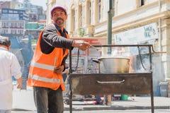 Mann, der Straßenlebensmittel zubereitet Stockfotos