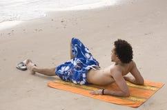 Mann, der am Strand ein Sonnenbad nimmt Stockbild