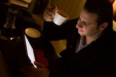Mann, der an Tablet-PC arbeitet und Kaffeetasse hält lizenzfreie stockfotos