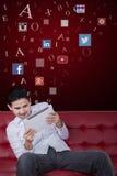 Mann, der Tablette auf Sofa mit Symbolen des Sozialen Netzes verwendet Stockfoto
