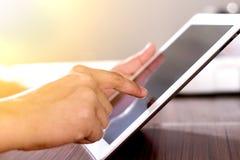 Mann, der Tablette auf Tabelle verwendet Lizenzfreie Stockbilder