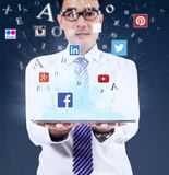 Mann, der Tablette mit Social Media-Symbolen hält Lizenzfreies Stockbild