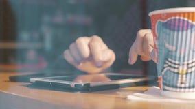 Mann, der Tablette verwendet und Kaffee im Caféfenster trinkt stock video footage