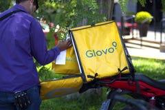 Mann, der Taschen innerhalb eines Glovo-Kastens setzt lizenzfreies stockfoto