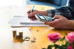 Mann, der Taschenrechner verwendet und Budget, Ausgaben und Einsparungen zählt Stockbilder