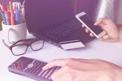 Mann, der Taschenrechner verwendet und Karte für Online-Zahlung mit Querstation hält Stockfotografie