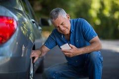 Mann, der Telefon bei der Prüfung von Rädern des Autos verwendet Stockfoto