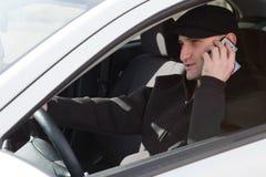 Mann, der am Telefon beim Antreiben spricht Stockfoto