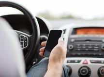 Mann, der Telefon beim Fahren des Autos verwendet Lizenzfreie Stockfotografie