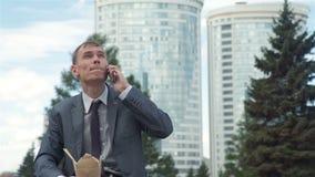 Mann, der am Telefon beim Haben des Mittagessen-Freiens spricht stock footage
