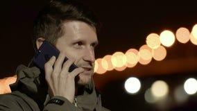 Mann, der am Telefon gegen Hintergrund der Nachtstadt spricht Es ist dunkel und kalt stock video