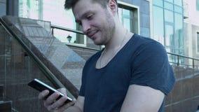 Mann, der am Telefon simst Ein junger Mann mit einem Smartphone schreibt sms nahe dem Gebäude Ein hübscher junger Mann in einem T stock footage