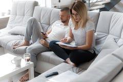 Mann, der Telefon verwendet Frau, die durch Dokumente schaut stockbilder