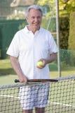 Mann, der Tennis und das Lächeln spielt Lizenzfreies Stockbild
