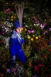 Mann in der teuren dunkelblauen Klage der Zauberkünstlerhaltung auf Blumenwiese. Lizenzfreie Stockfotos