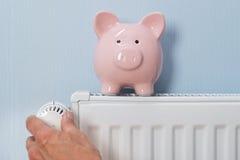 Mann, der Thermostat mit Sparschwein auf Heizkörper hält Lizenzfreies Stockfoto