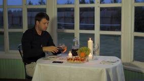 Mann, der am Tisch, trinkender Rotwein, den Canape essend sitzt und rufen den Kellner an stock video footage